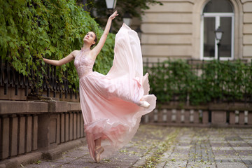 Young beautiful ballerina posing outdoor