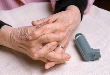Woman's hands and asthma inhaler