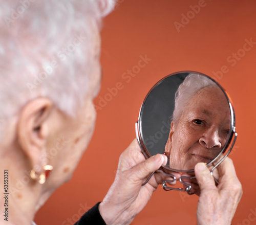 Portrait of old woman looking into a mirror