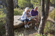 aging couple having a break while hiking in the countrysi