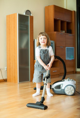 girl with vacuum cleaner on parquet