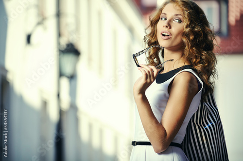 fashionable girl in white dress with shopping bag