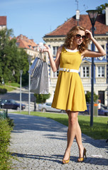 fashionable girl in yellow dress with shopping bag a old city st