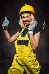 Attractive smiling builder woman with hammer showing thumbs up