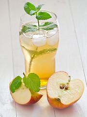 Apfelschorle mit Apfelspalten auf einem weißen Holztablett