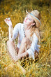 blond woman sitting down outdoor on the yellow grass with a hat