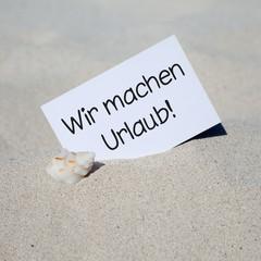 Muschel im Sand mit Karte WIR MACHEN URLAUB!