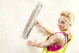 Female with putty knife working indoors poster