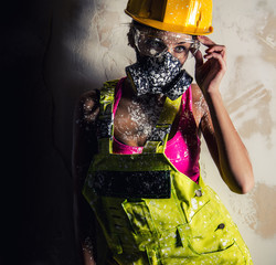 Female construction worker wearing a respirator posing indoors