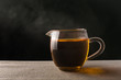 Hot black tea in glass on dark background