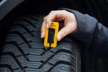 Frau misst Reifenprofil eines Autoreifen