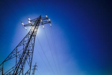 Strommast mit Sonne vor blauem Himmel