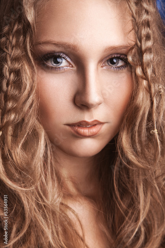 Portrait of charming young woman with curly brown hair