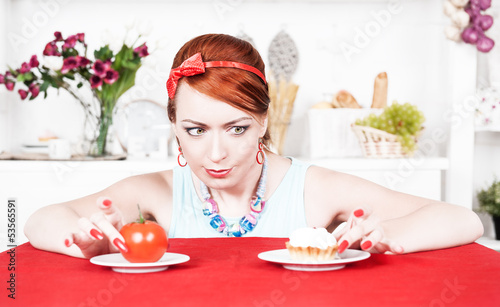 Woman choosing between healthy food and cake