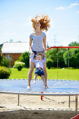 Young mother and little daughter bouncing on trampoline