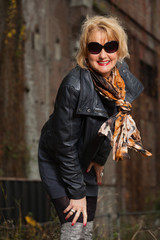 Pretty middle aged woman with blonde hair and black sunglasses.