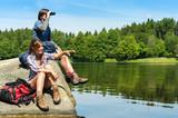Teenage hikers birdwatching at lake poster