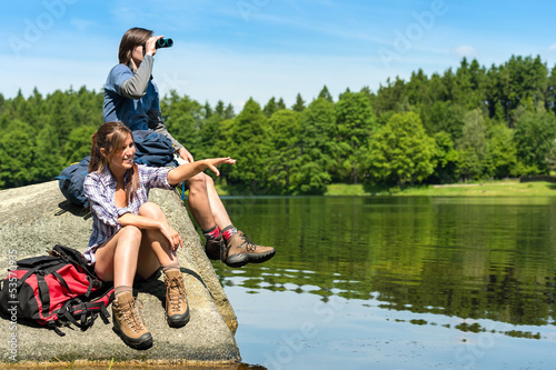 Teenage hikers birdwatching at lake