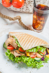Kebab in grilled pita bread next to cold beverage