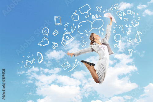 Businesswoman holding papers and jumping