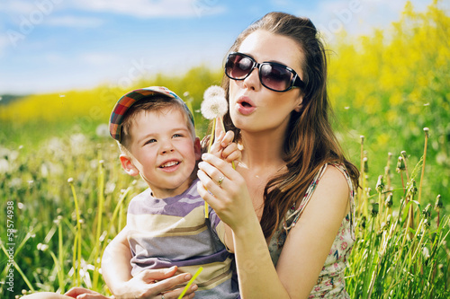 Pretty young mother playing dandelions with son