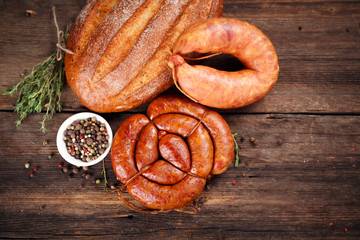 Sausage, bread and spices on wooden surface