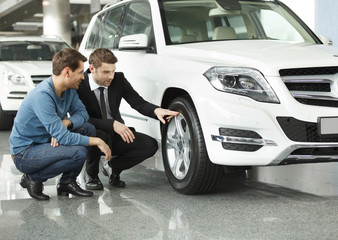 Look at these tires! Young car salesman showing the advantages o