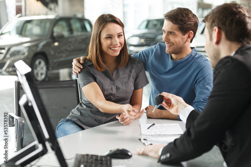 Now her dream comes true. Car salesman giving the key of the new - 53578392