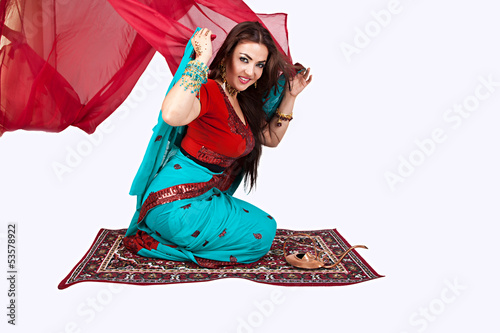 Beautiful young indian woman sitting on a flying carpet