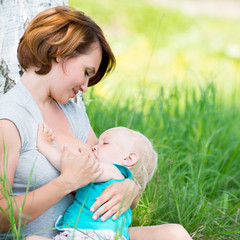 Young mother breastfeeding a baby in nature