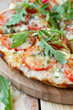 pizza with tomatoes, cheese and arugula