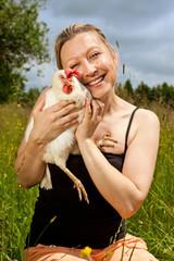Frau schmiegt sich an Henne
