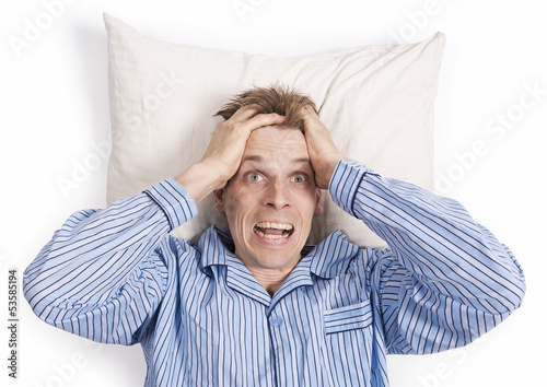 Stressed man in bed with hands in hair