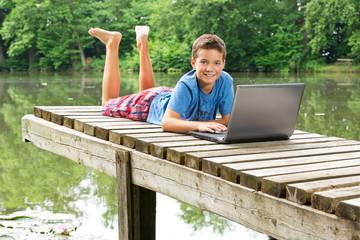 Freundlicher Jungendlicher mit Notebook am idyllischen Teich