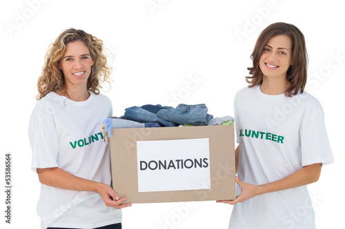 Two cheerful volunteers carrying clothes donation box