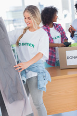 Smiling volunteers putting clothes in clothes rail