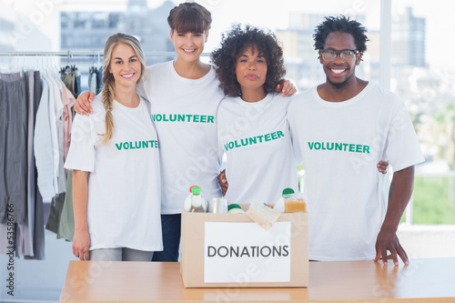 Volunteers standing in front of food in a donation box