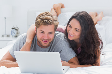 Attractive woman embracing husband while using a laptop