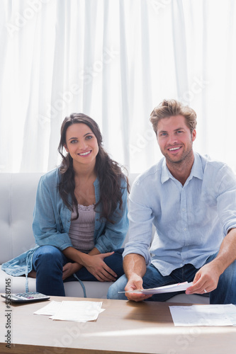 Couple smiling while doing their accounts