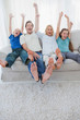 Portrait of a family watching television and raising arms