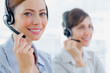 Smiling call centre agents with headsets at work