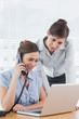 Businesswoman phoning and looking at laptop with colleague