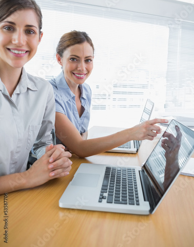 Businesswoman pointing to something on laptop for colleague port