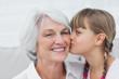 Cute little girl kissing her grandmother