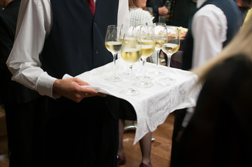waiter carrying tray with wine glasses
