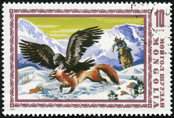 stamp printed by Mongolia, shows golden eagle hunting fox