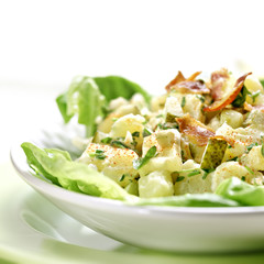 Potato salad with bacon on a green plate