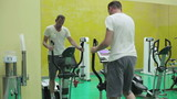 Young man at the gym exercising on the xtrainer machines