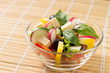 Fresh Salad in a Glass Bowl on Bamboo background