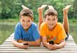 Zwei jungendliche Freunde mit Smartphone am idyllischen Teich